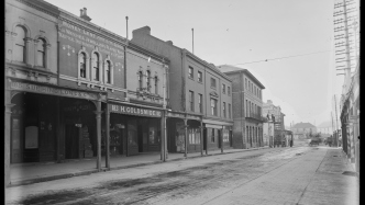 This is a black and white photograph of an empty street with shopfronts and covered awnings.