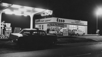 Black and white photograph of illuminated Esso service station at night, with car in foreground.