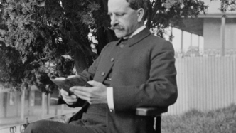 Black and white photo of seated man in garden.