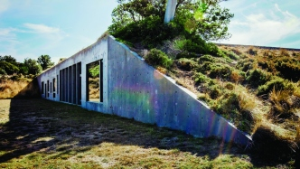 Exterior of the Phillip Island House set into the landscape with hardy grasses growing over the roof