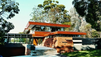 This is a front three-quarter photograph of a modernist 1950s house with a timber, glass and red-brick frontage and 5 low concrete stairs leading up to the front door