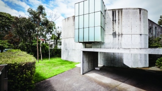 This is a photograph of a oval shaped concrete building with a large square glass room protruding at the front of the building. The house is surrounded by grass and trees.