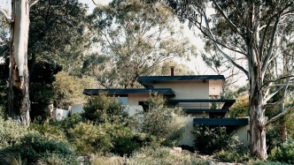 This is a photograph of a split level house set among tress and a natural bush landscape
