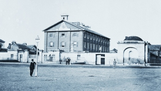 Black and white photo of barracks from across gravel road. Man leaning on lamppost in foreground. Windows of barracks have shutters and the bottom three front facing ones have blinds visible.
