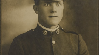 Photograph of young man in uniform including cap.