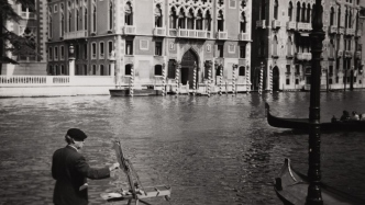 This is a photograph of a man in a beret standing by a canal in Venice with an easel painting. Venetian palazzos and gondolas are in the background