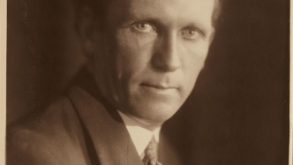 This is a black and white portrait photograph of the head and shoulders of a man in his mid 40s