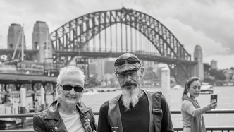 Couple in front of ferry wharves and another woman in background, with Sydney Harbour Bridge as backdrop.