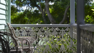 Detail of ironwork and cane chairs on sunny verandah.