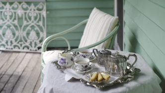Small table, covered with white tablecloth, on verandah, with tea tray holding two tea cups, teapot, sugar bowl, milk jug and biscuits,