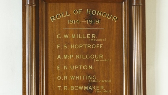 Wooden carved honour roll with gold lettering.