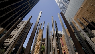 A photo taken looking up at a 45 degree angle at the edge of the tres sculpture. The poles that are a part of it appear to stand along side the buildings