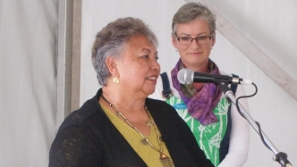 Woman speaking into microphone with another woman in background looking on.