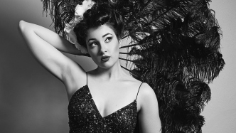 Image of Bella Louche holding a feather fan behind her head