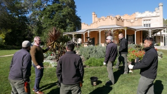 Ian Innes and the horticulture team discussing rose pruning techniques in front of Vaucluse Hosue