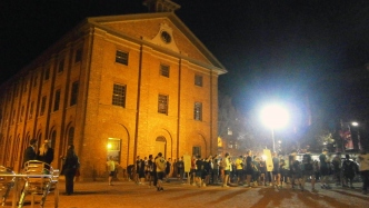Group of people illuminated by floodlights in the courtyard, with the barracks building behind.