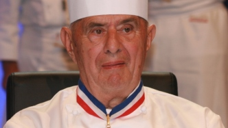 A man in a chef's hat and whites with a medallion around his neck