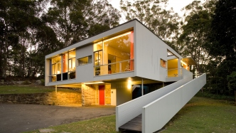 Photo of Rose Seidler house at night with lights shinning through windows