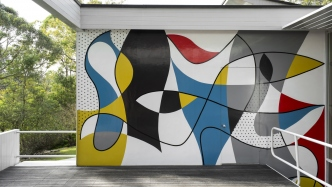Colourful modernist mural on wall of house.