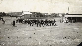 Group of men in formation in middle ground of large open area with buildings behind.