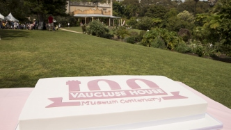 Pink iced cake with 100 years emblem on it, with house in background.