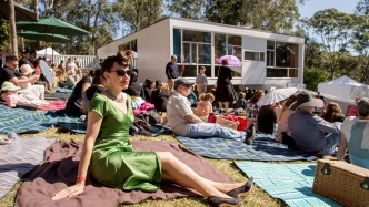 Large group of people with picnic rugs on sloping lawn with house in background.