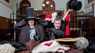 Two little boys dress up in an old court room