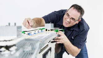 Lego expert Ryan McNaught placing LEGO bricks on large scale LEGO model of Marina Bay Sands