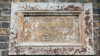 Closeup of carved stone wall plaque with words 'Susannah Place Anno Domini 1840' inscribed.