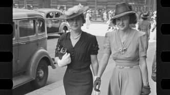 Black and white photo of two women in street.
