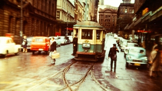 Colourful image of a green and yellow tram making its way down Sydney city street.