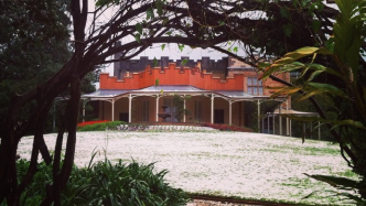 View uphill across lawn covered in hail stones, surrounding an ornate fountain, with single story yellow mansion with large verandah and leafy garden behind.