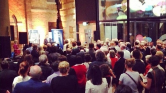 A large crowd look on at SLM director Mark Goggin speaking in the foyer of the Museum of Sydney foyer.