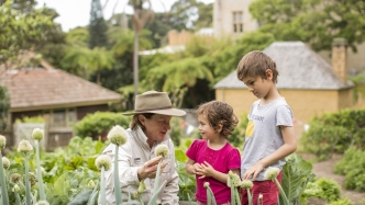 Woman in gardening gear talking to two kids in garden setting.