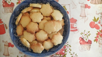 Plate of flower shaped biscuits on patterned tablecloth.