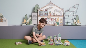 Child in exhibition space interacting with model cars and trucks.