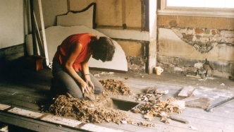 Person in red shirt kneeling in front of lifted floorboards removing debris.