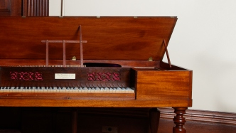Square shaped piano with lid open and music stand up.