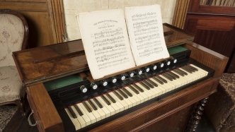 Musical instrument with music book open on stand above keyboard.