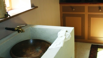 Square stone sink with brass tap in front of open window, with brown painted timber dresser in the background.