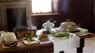 Wooden kitchen table at Vaucluse House  with jelly, fish, sauce boat, electro-plated dish and cover, soup tureen, Bain-Marie pan and pots and cloth covered mixing bowl