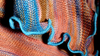 This is a photograph showing the edge of a knitted garment made from yarn in blue, orange, red, brown and pink