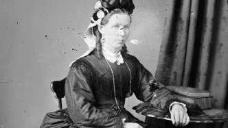 Black and white photo of woman in formal dress.