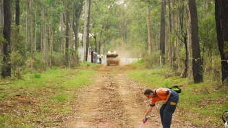 Man on bush track bending down to spray marks on surface of track.