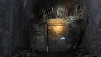 Moodily lit circular tunnel with doorway and wire.