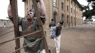 A man is is being flogged against the flogging triangle while an overseer watches on