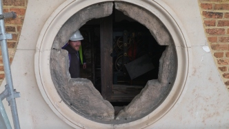 Photo showing the hole left in the pediment of the Hyde Park Barracks after the clock face was removed. A man in a hard hat can be seen staring our.