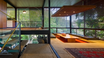 Photo looking across the interior of a modernist house. A stair can be seen and a sunken dining area.