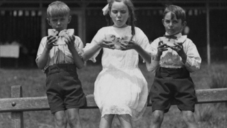 Black and white photo of three children sitting on a fence eating watermelon slices.