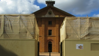 Entrance gates to museum with scaffolding over two gatehouses.